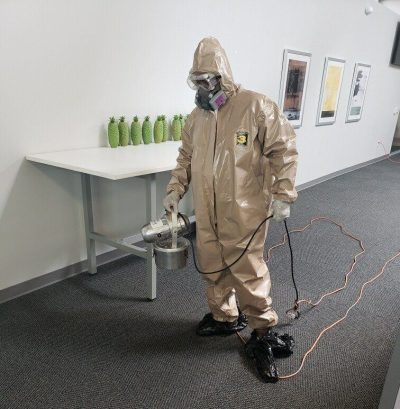 professional cleaning technician wearing ppe and disinfecting an office from COVID-19