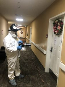A man wearning perpersonal protective gear is cleaning a facility of covid-19 using a thermal fogger