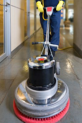 professional janitorial service cleaning the floors with a machine scrubber
