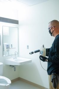 Tech applying Microshield 360 Antimicrobial in a restroom